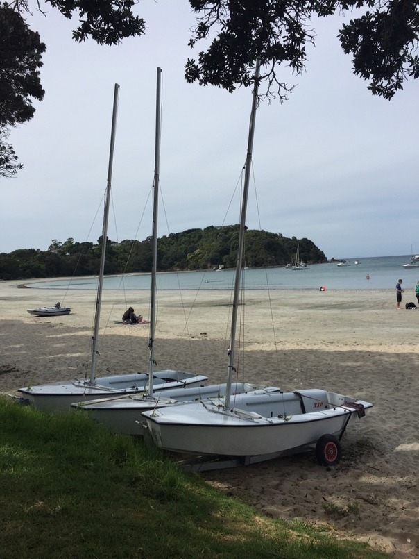 small sailboats dragged up on the sands of a cove